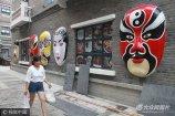 """2017年7月5日,在济南泉城路红尚坊,现极具传统文化味的""""京剧脸谱""""墙,吸引众多路人的眼球。"""