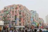 2017年7月5日,青岛,台东商业步行街,道路两旁的十余栋居民楼的墙体画满大型墙绘,这些手绘图案高达七层楼,除了窗户玻璃,居民楼墙体其余部分全部被图案覆盖。