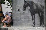 2017年7年6日,山东济南,曲水亭街墙体一匹3d马,栩栩如生,路过此处市民驻足抚摸观看。