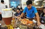 """*2017年8月10日,山东青岛金沙滩啤酒城啤酒屋,店员在给顾客上""""海鲜大咖""""。"""