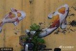2017年8月16日,济南天桥区万盛街胡同里,不少年岁旧的老房子墙体上描绘上数百条锦鲤,变身艺术墙,由于形态各异活灵活现的鱼儿十分醒目,吸引众多路人的眼球。