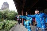 80后小伙赵庆因为太极打得好,再加上能说一口流利的英语,不少来西安旅游的老外都会跟着他体验中国太极拳的魅力。图为赵庆在小雁塔教外国小游客打太极拳。