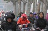 2017年12月14日,济南迎来今冬首场降雪。在山东济南泉城路上,众多市民冒着雪出行上班。