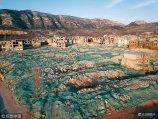 2017年12月12日,济南,航拍镜头下的大涧沟村,数千栋房屋已经拆除过半,房屋旧址盖上了防尘网。