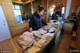 2018年2月4日,黑龙江漠河。在北极村内的中国最北邮政局内,近百名游客在挑选明信片等邮政纪念品,还有的在使用电脑,打印自己此行的照片。
