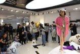 """2018年3月19日,杭州,一位""""穿版模特""""吸引多人围观。在浙江杭州四季青服装市场,不少商铺的""""穿版模特""""会在店铺搭台试穿衣服,以现场展示服装的方式来进行促销。"""