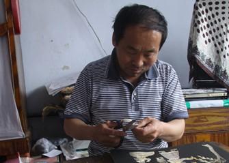 孙玉林正在制作鱼皮画