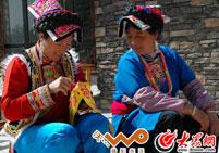 两位羌族妇女在探讨绣花技术