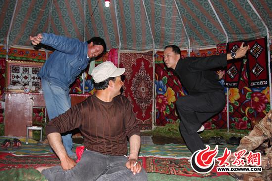 采访团成员王伟和塔吉克族朋友一起跳鹰舞