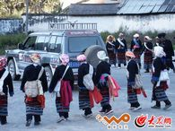 佤族群众围着采访车以民族歌舞欢迎