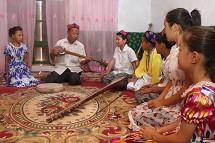 老人教孩子弹唱吐鲁番十二木卡姆