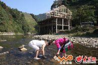 潘永艳与小记者莹莹在家门前的金江里捉鱼