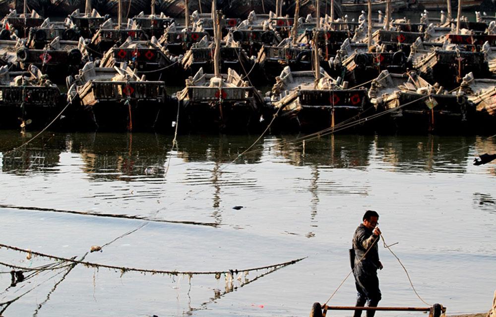 """2014年5月1日,山东省日照市,贴着""""福""""字的渔船整齐排列,一位渔民正在海边,准备出海。(日照站 李佩强摄)"""