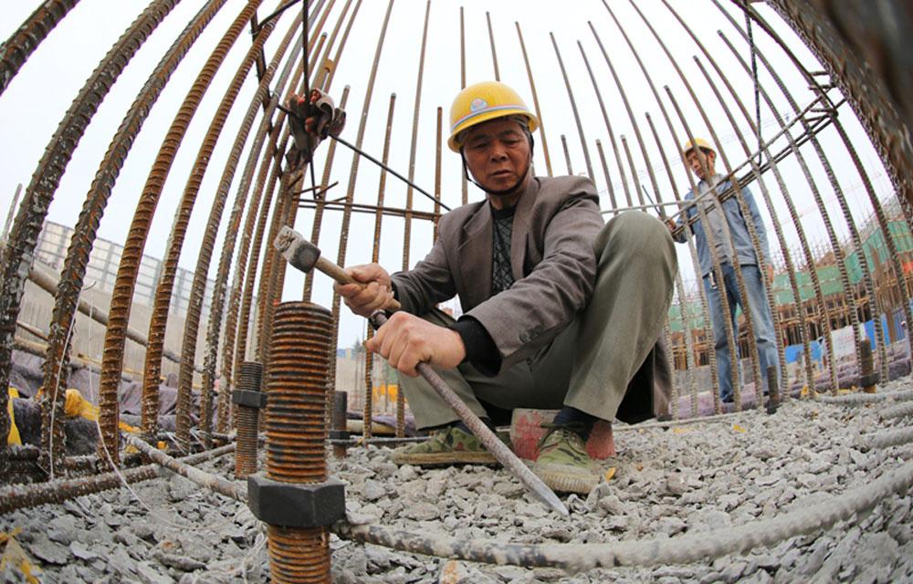 ?2014年5月1日,山东省日照市,位于世帆基地的兴业喜来登广场建筑工地,建筑工人正在施工。(日照站 李佩强摄)