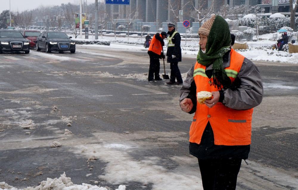 从清晨四点到上午九点,暴雪中的环卫工已工作了五个小时,吞食冰冷的早餐面包,是今天最奢侈的愿望。