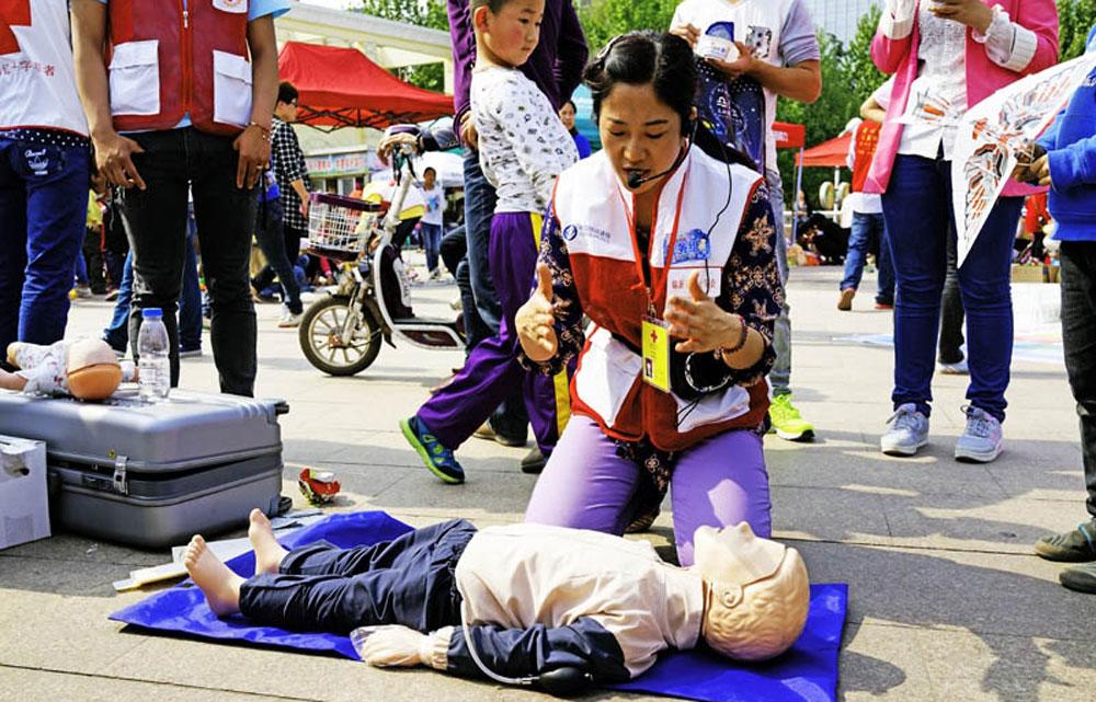 2014年5月1日,一位红十字会志愿人员在临沂人民广场宣传街头救护知识。