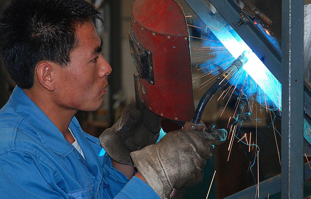 5月2日,日照兴业汽车配件有限公司,车间工人正在生产重型汽车底盘。进入2014年,该公司汽车配件定单充足,满负荷运转。