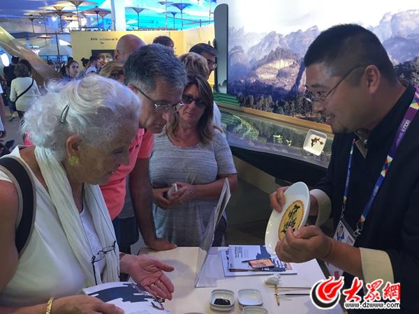 东明粮画技艺传承人韩国瑞正在为意大利游客介绍东明粮画制作过程.