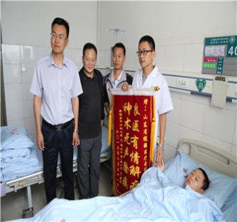 山大二院医务部副主任、小儿外科专家王若义接过第一例手术患者刘敬家人送给的锦旗.JPG