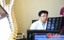 8、一个人体脊柱模型一个CT片阅片机,师彬的办公桌和其他医生无异,在门诊处的角落里。大众网记者 王长坤 马俊骥 摄.jpg