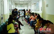 conew_4月25日上午,山东省立医院西院区妇产科门诊外,来此诊疗的患者们等候在走廊两侧的长椅上。大众网记者 王长坤 马俊骥 摄.jpg