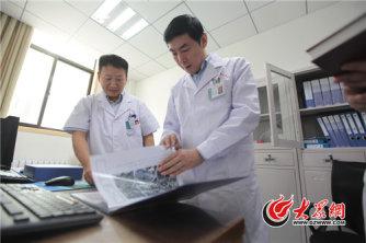 山大二院院长赵升田和医生一起查看伽马刀治疗案例。大众网记者 王长坤 马俊骥 摄.jpg
