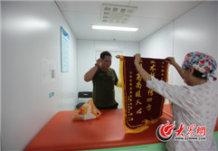 """5月18日,在山大二院新生儿重症监护室外,一名患儿家属将一面锦旗送到医护人员手中,激动地说:""""谢谢你们所有人。""""山大二院的医疗服务标准化给众多患者留下了深刻印象。大众网记者 马俊骥 王长坤 摄.jpg"""