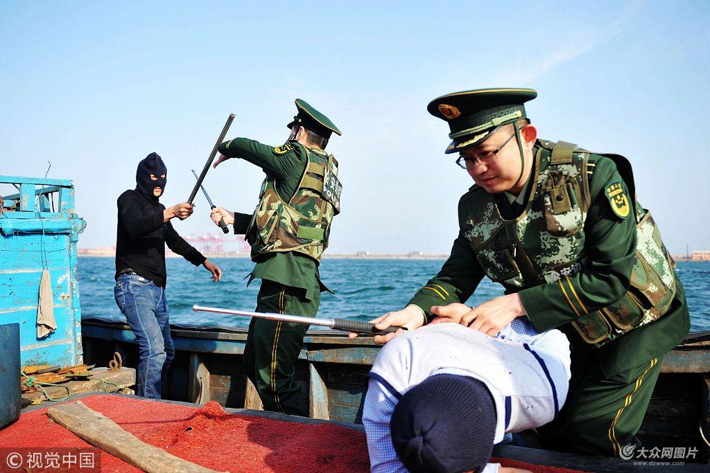 2018年4月9日,山东青岛西海岸新区董家口港,黄岛边检站干警制服渔船