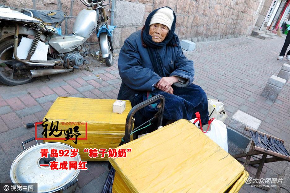 """11月24日,青岛莱芜二路靠近齐东路路口,媒体和爱心市民围绕着在此摆摊卖粽子的92岁老人宋学蓝,当天早晨她带来的100多个粽子瞬间被爱心市民""""秒杀"""",大家都希望她能早点回家。"""