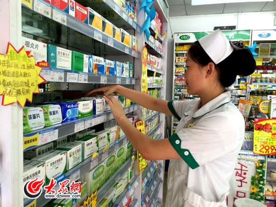8月9日下午,在济南泉城路附近的一家药店内,店员正在整理货架上的药品,1.8元一盒的维C银翘片被放在货架的最底层。记者 马俊骥 摄.jpg