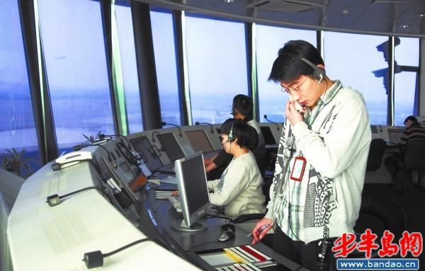 塔台管制室内,一名管制员在指挥飞机滑行到跑道