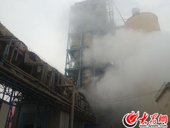午,在淄博宝山水泥厂,伴随着转动的回转窑,雾霾和水泥生产产生图片