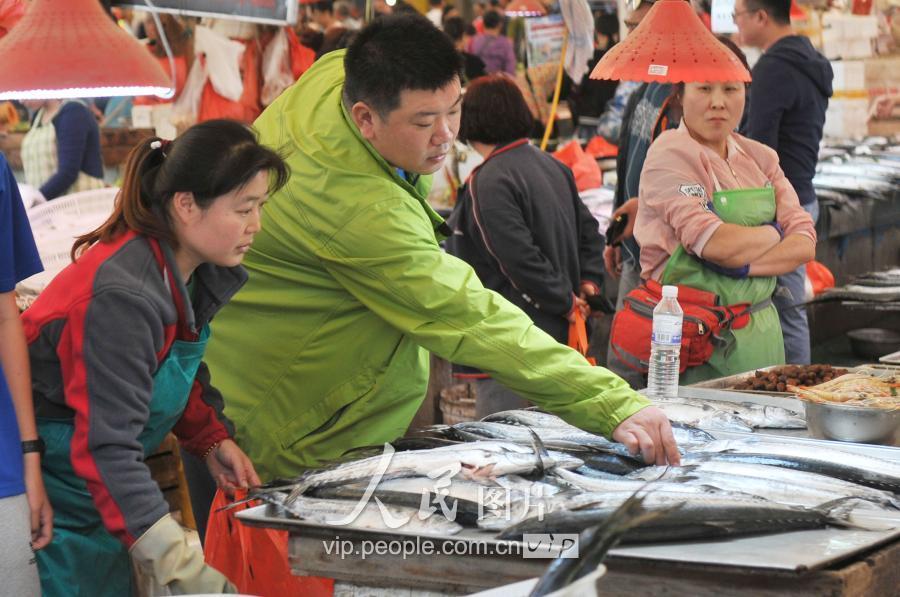 青岛市镇江路市场海鲜摊位摆满休渔期前捕获的新鲜的春鲅鱼.