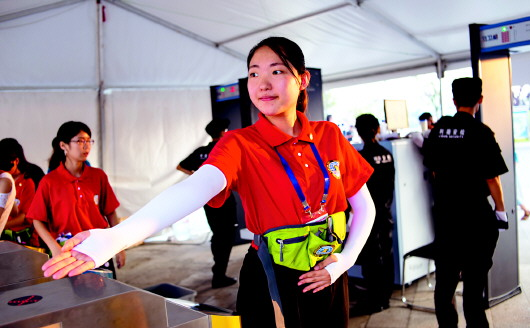 志愿者做出迎宾手势,要求手臂与身体呈规定角度.