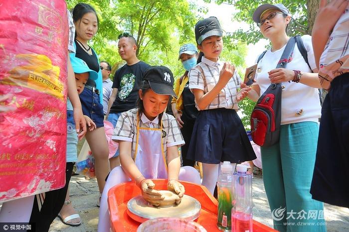 小学生在体验传统泥塑制作过程.
