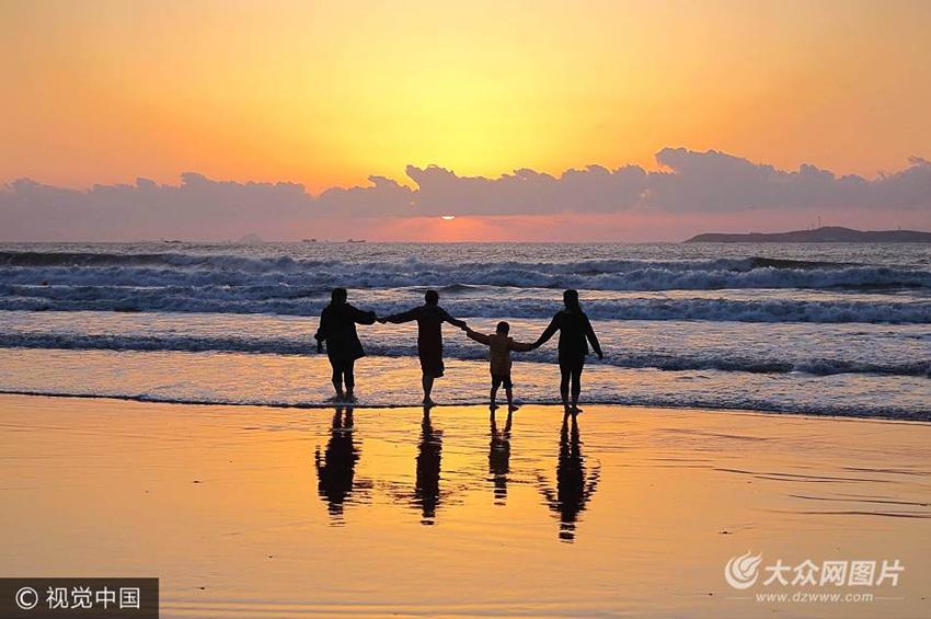 2017年10月2日,山东青岛市,游客在金沙滩看日出.