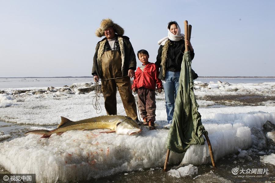 """赫哲族是中国人口较少的民族之一,主要分布在黑龙江、松花江和乌苏里江流域,是我国北方唯一以捕鱼为生和使用狗拉雪撬的民族,历史称其为""""生女真""""、""""鱼皮部""""和""""使犬部""""。图片作者:肖殿昌/视觉中国"""