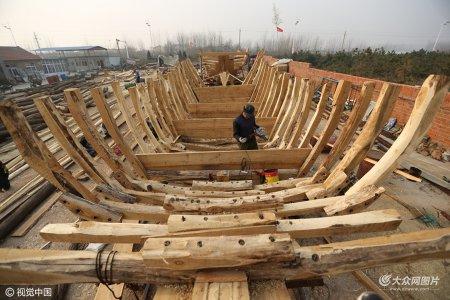 2016年12月4日,日照,山海天旅游度假区任家台村海边,8位老师傅在用传统的手法造木渔船。
