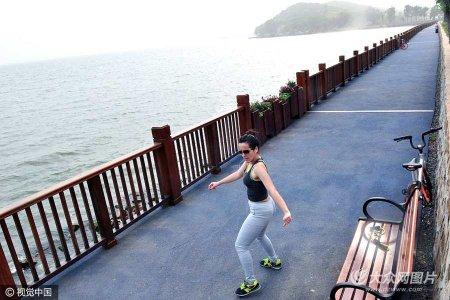 :2017年5月6日,武汉,一位外国美女戴着耳机在东湖边独舞,吸引过路行人关注。