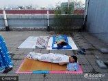 2017年6月1日,河南郑州,一高校的不少学生为避暑,纷纷带着凉席被褥到楼顶天台打地铺过夜,还有学生在楼顶支起帐篷睡觉。