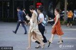 """2017年6月9日,北京最高气温达37℃,""""高烤""""模式继续,三里街区的爱美女士屯身着清凉夏衣出行。"""