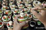 2017年6月9日,山东省临沂市郯城县港上镇樊埝村村民为木旋玩具上彩。