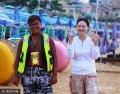 8月19日,威海。张杰今年不到20岁,是一名在校大学生。趁着暑假在海边打工赚钱的他,虽说才工作了短短一个月,但他与游客站在一起时,强烈的肤色对比给人带来的视觉冲击力足够震撼。