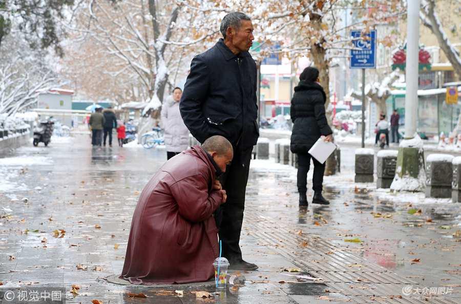 洛阳:两位民工大雪中轮流蹲热力井盖蹭暖