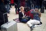 """2018年1月19日下午,北京,两名从来没有感受过""""春运""""气氛的荷兰美女,因排队时间太久、无法忍受双腿酸痛,干脆铺上衣服瘫坐在地上。"""