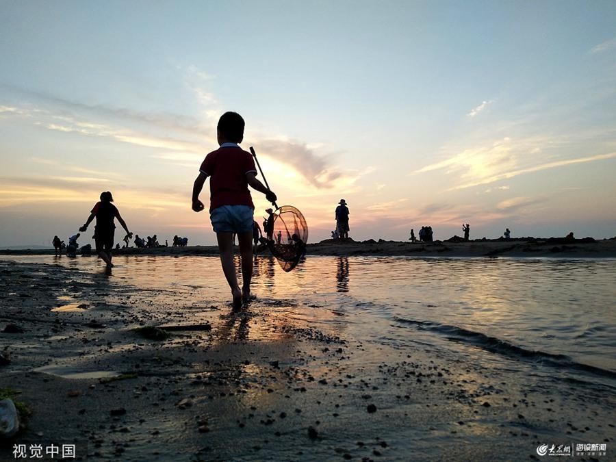 2019年7月23日,山东威海,当日是大暑时节,游客纷纷到那香海海边避暑游玩,夕阳西下剪影美如画。
