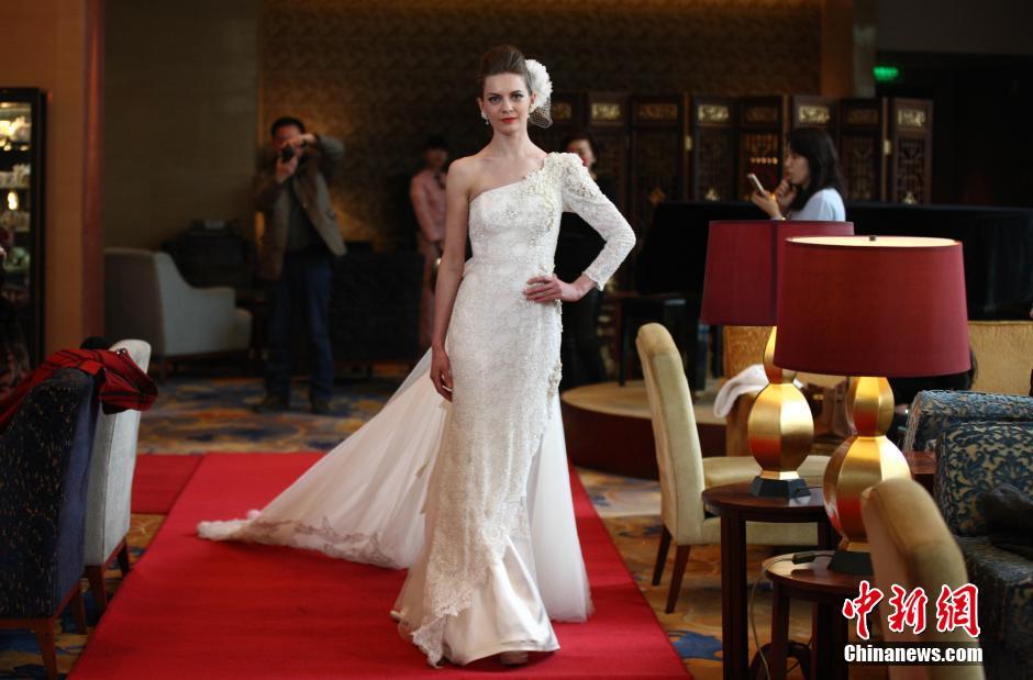 """3月9日下午,在青岛香格里拉大酒店大堂酒廊里,举行了一场别开生面的婚纱展演,四名""""老外""""模特身着婚纱在座位之间串行,为客人们奉上一场近距离的视觉盛宴。"""