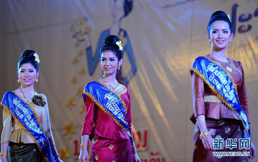 """3月15日,在老挝首都万象塔銮广场,身着老挝传统服装的选手们参加""""宋干小姐""""评选。新华社发(刘艾伦摄)"""
