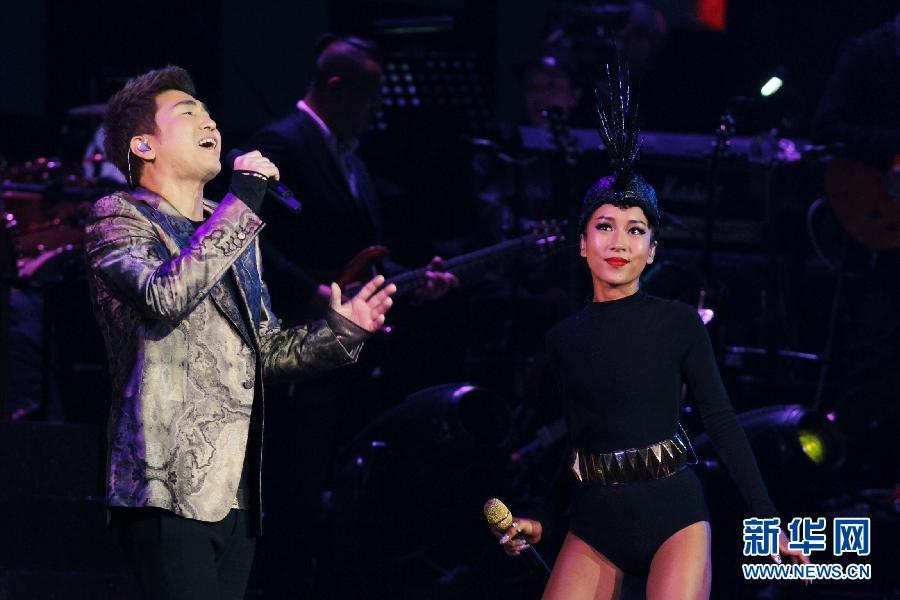 """3月23日,吉克隽逸和助演嘉宾沙宝亮(左)在演唱会上合唱歌曲。 当日,歌手吉克隽逸的首场个人演唱会""""即刻出发""""在北京工人体育馆举行。新华社发"""