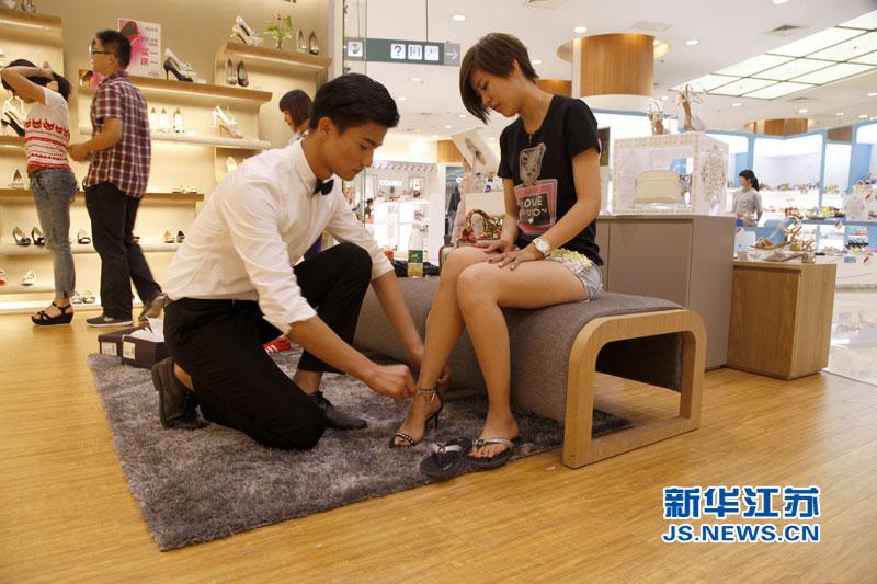 5月31日,男模正在为顾客试穿高跟鞋。